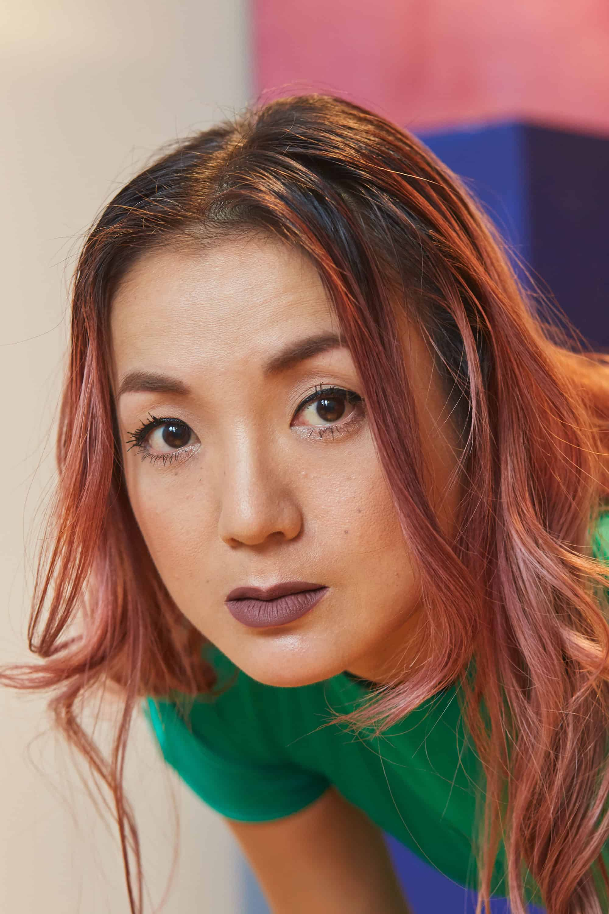 """Close-up portrait of Japanese woman, wearing green dress. Pink and purple highlights in her hair. Plinths in the background."""