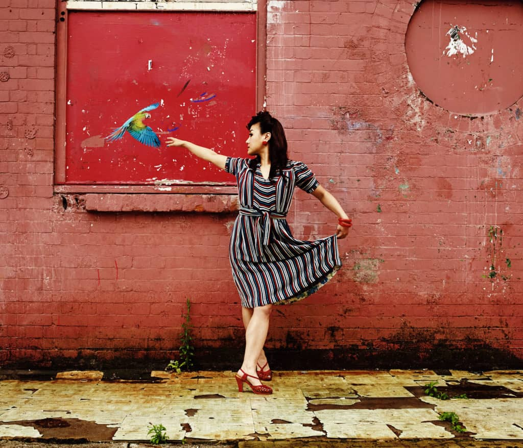 """""""Location portrait of Lindy Hop dancer posing in-front of a weathered wall. A picture of a parrot flies towards her as she makes a ballet shape. Wearing a vintage dress."""""""
