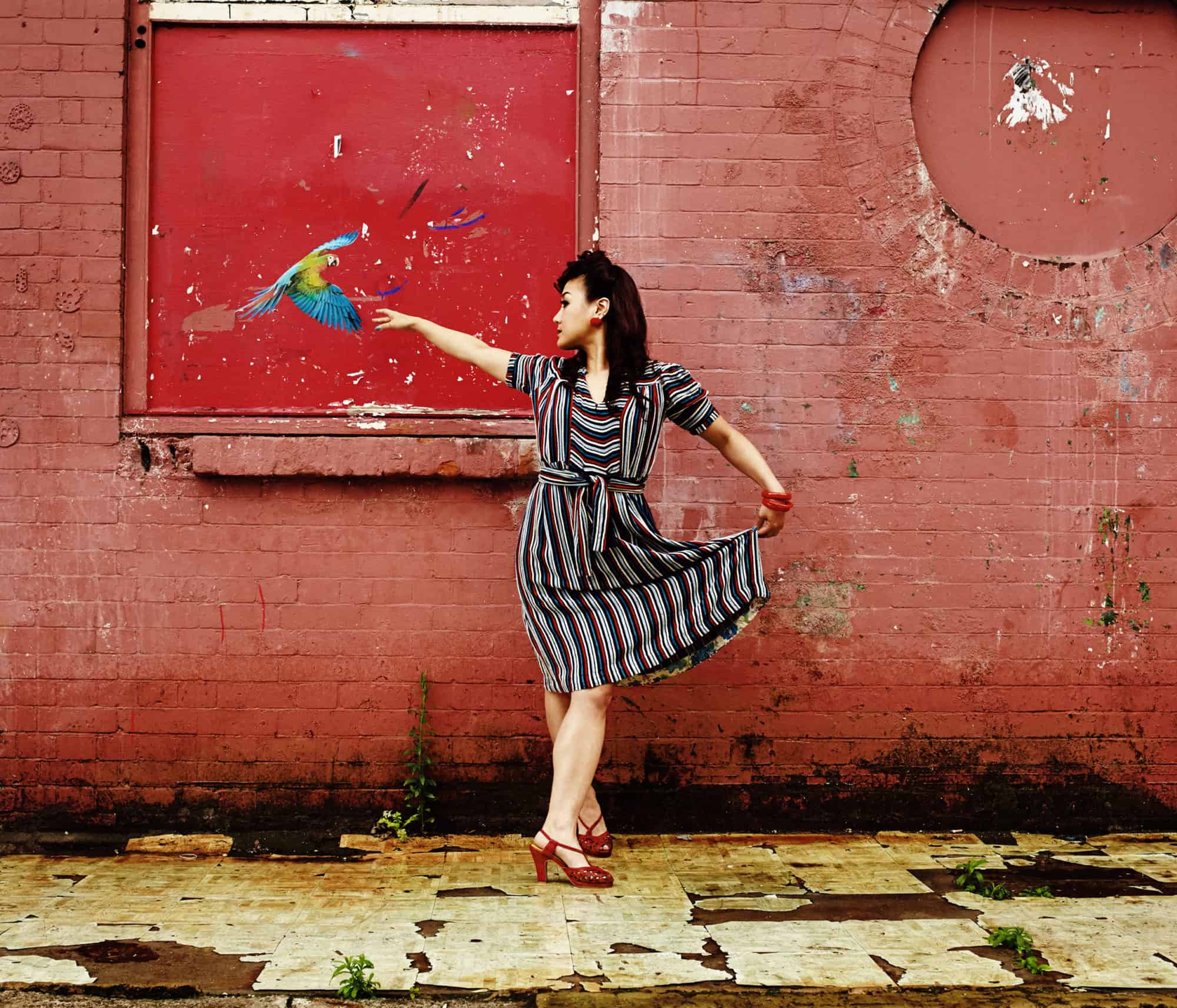 """Location portrait of Lindy Hop dancer posing in-front of a weathered wall. A picture of a parrot flies towards her as she makes a ballet shape. Wearing a vintage dress."""