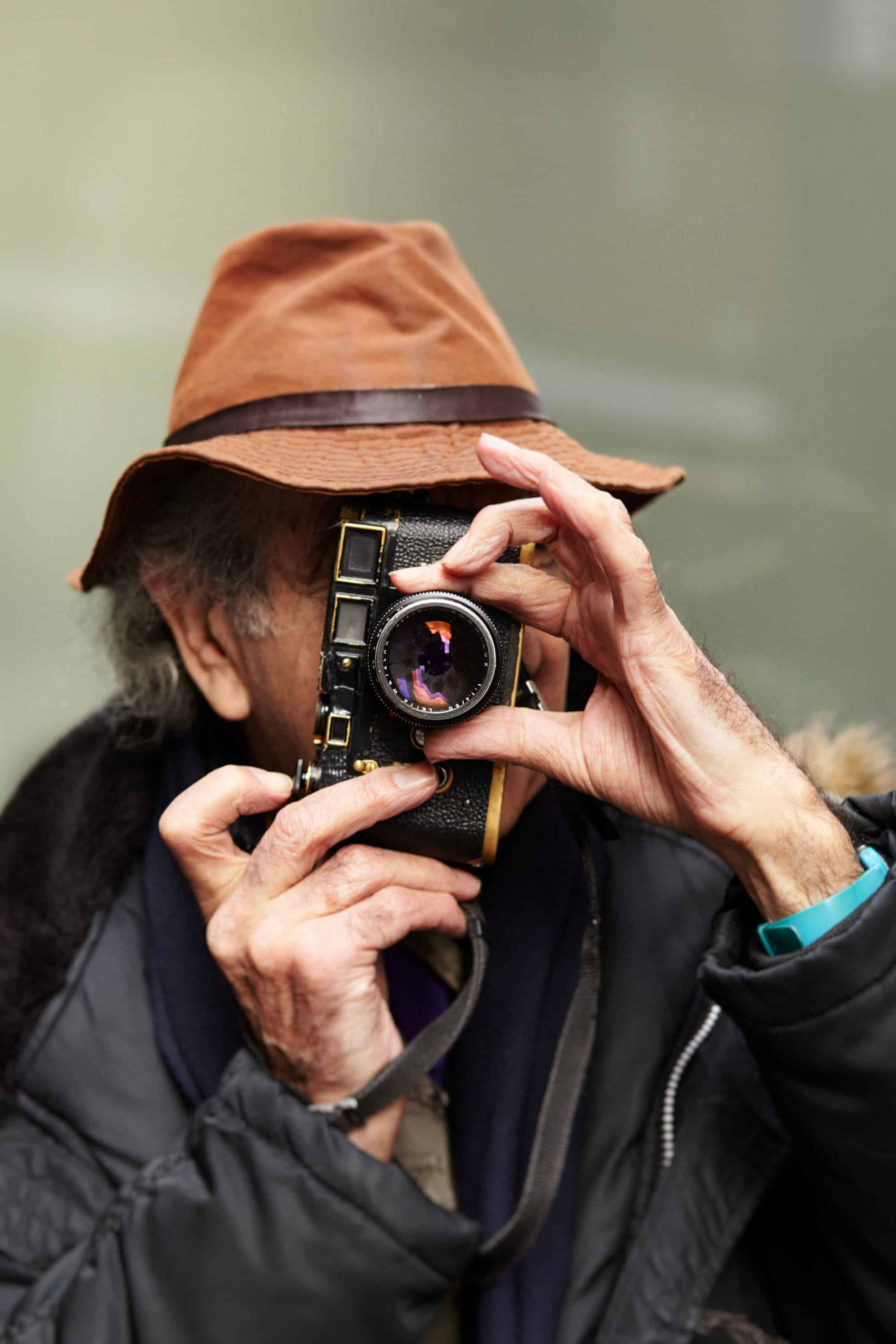 """Action portrait of Neil Libbert taking a picture with an old Leica rangefinder camera. His hands elegantly operating the controls. Blurry out of focus green background."""