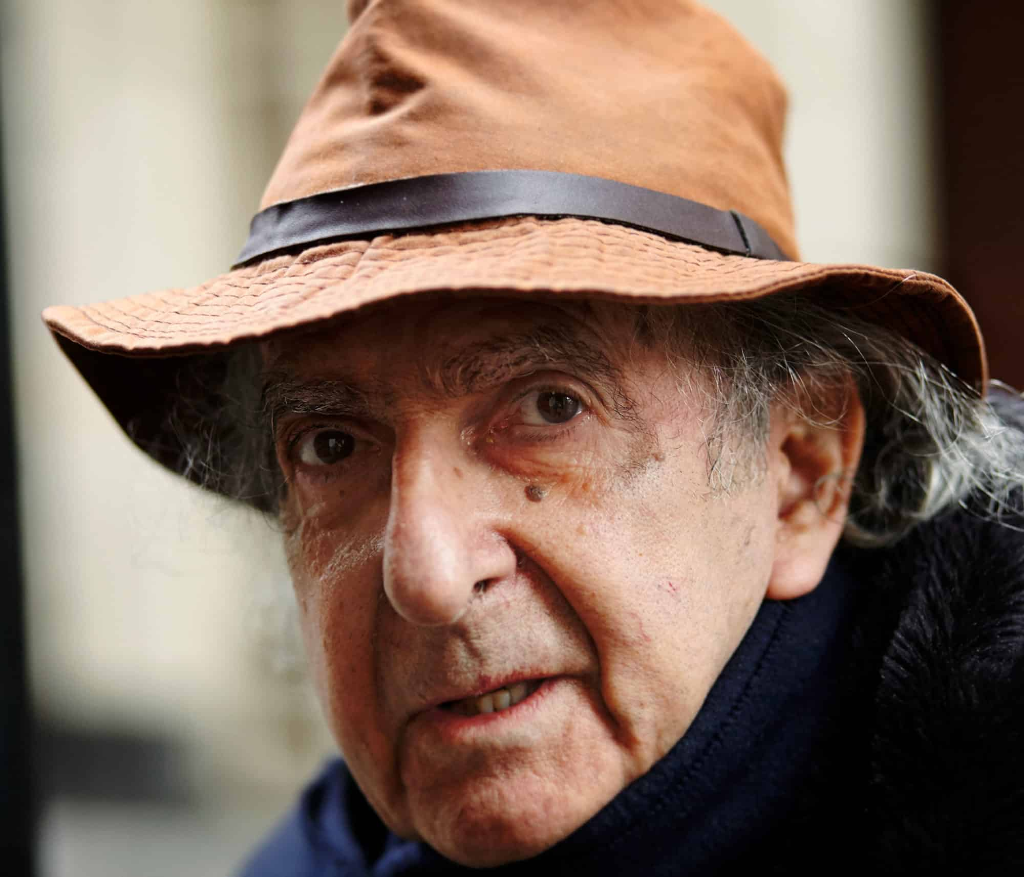 """Close-up intimate portrait Neil Libbert. Senior photo-journalist wearing brown hat with leather strap. Grey hair. Looking directly into camera. Blurry background."""