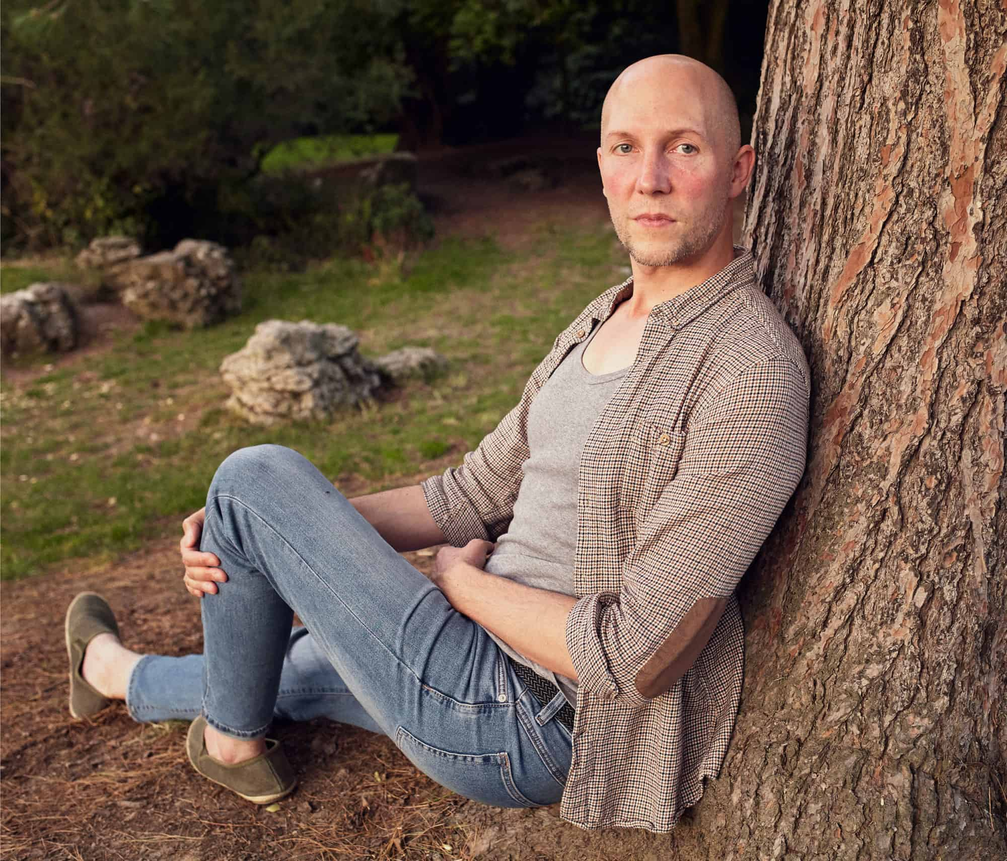 """Portrait of expressive thirty-something year old man with bold head. He rests on the trunk of a large tree, in a well kept park. He is wearing a tightly checked shirt, blue jeans and slip on shoes."""