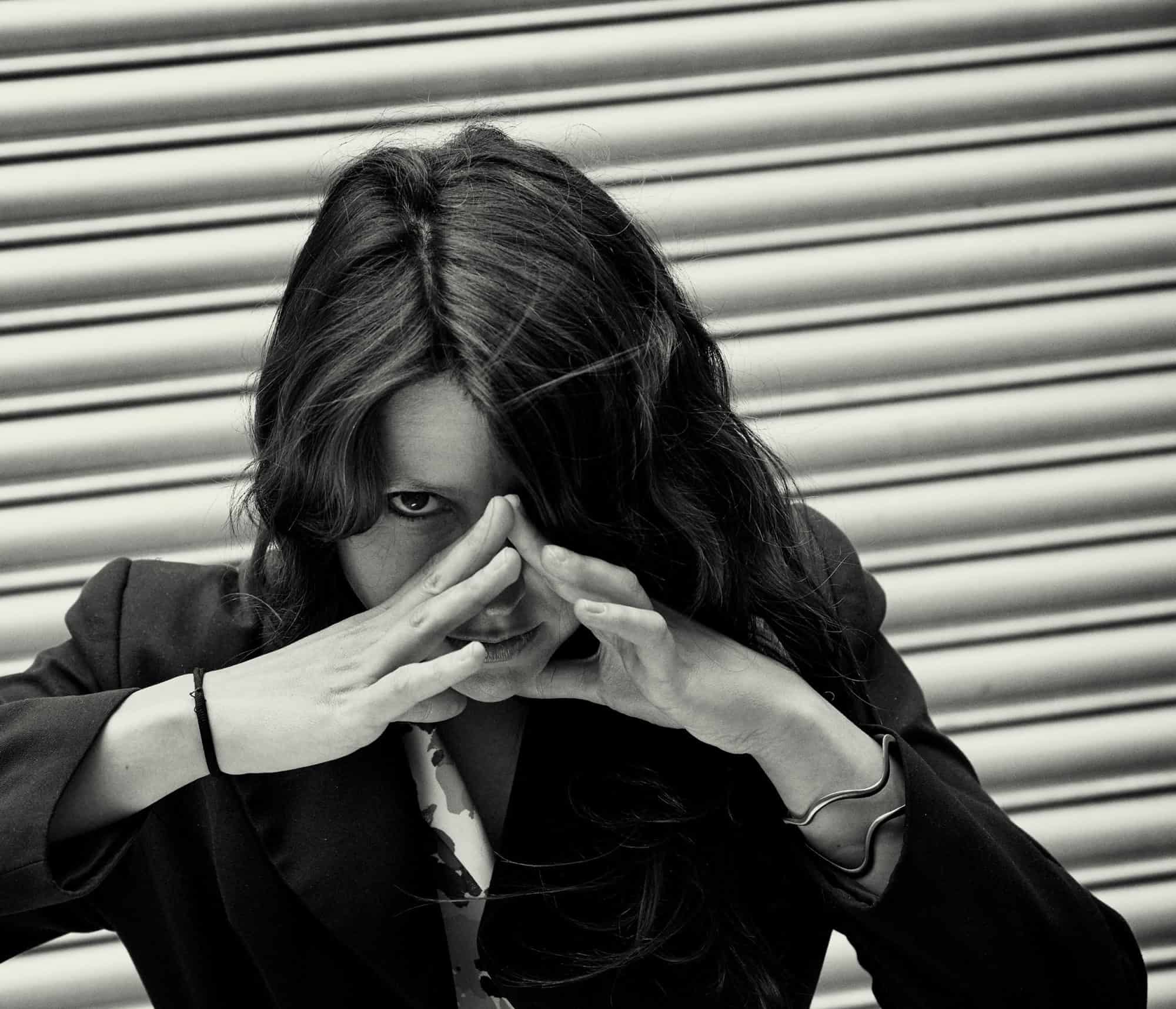 """Portrait of stylish woman in-front of closed shutters. She is making a triangle shape with her hands. Wearing a black jacket."