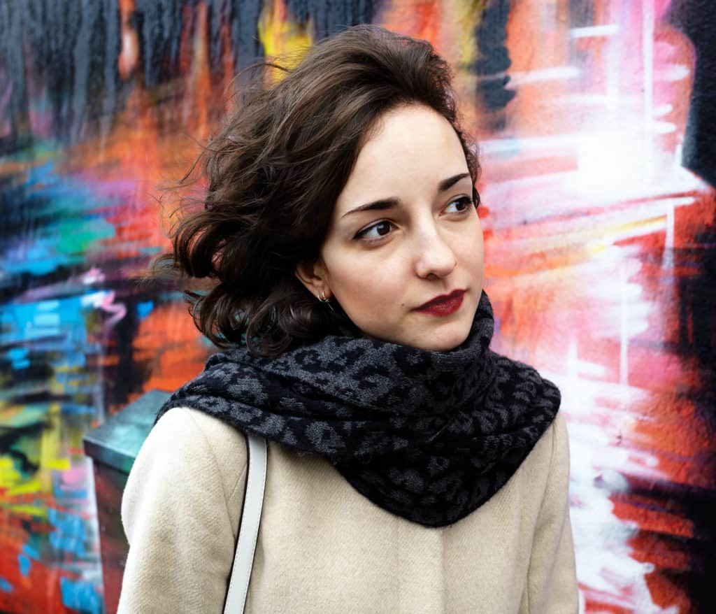 """""""Movement portrait of young Spanish woman passing a brightly coloured wall in Camden Town, London. Wearing black scarf and white winter coat."""""""