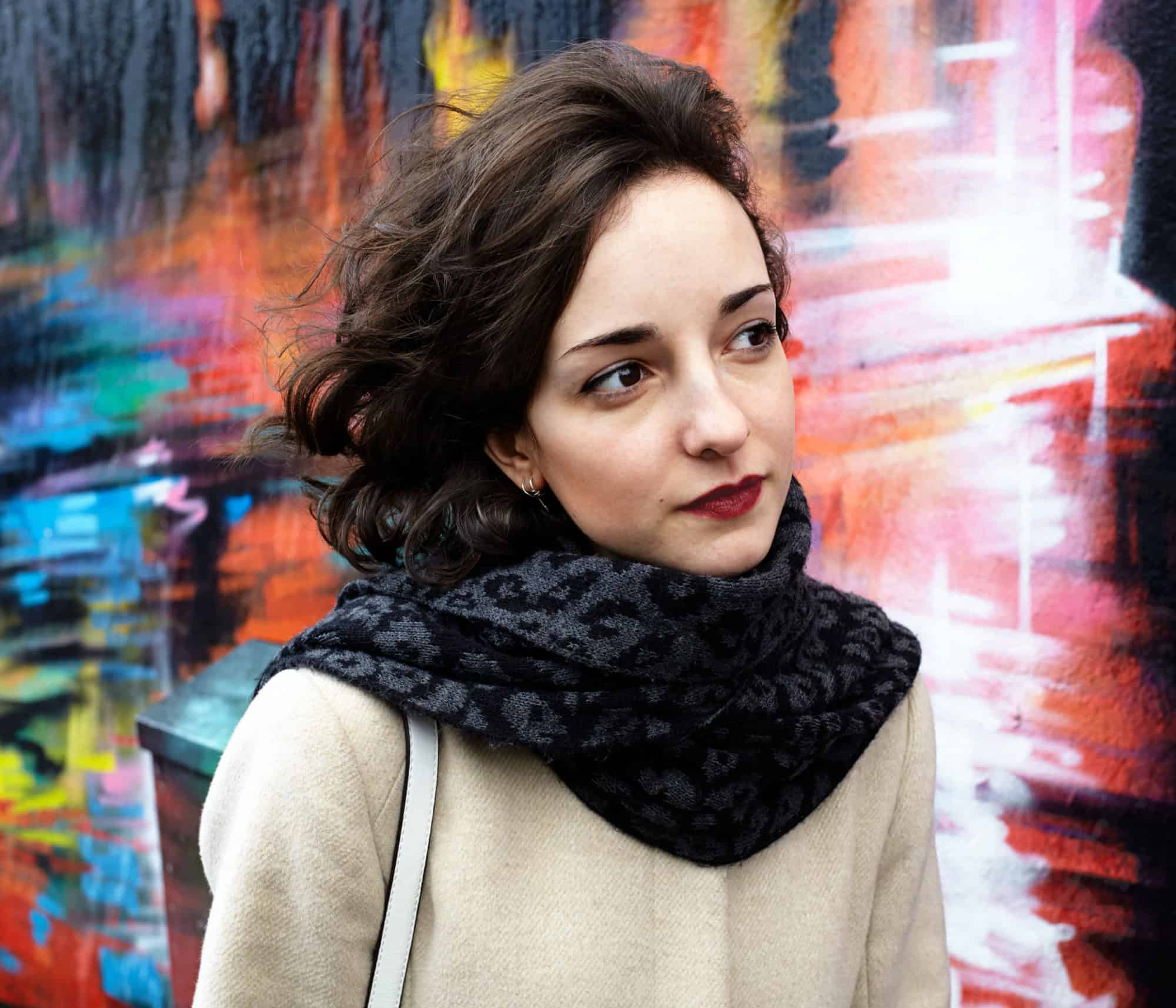"""Movement portrait of young Spanish woman passing a brightly coloured wall in Camden Town, London. Wearing black scarf and white winter coat."""