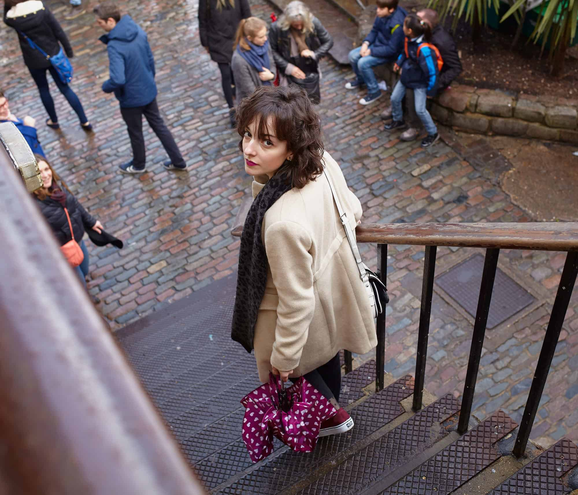 """Portrait of young Spanish girl walked down steps into Camden Market. Wearing white winter jacket. Carrying burgundy collapsed purple umbrella."""