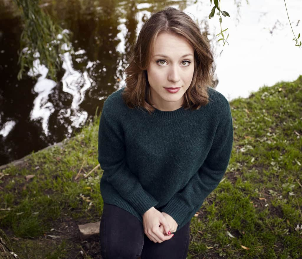 """""""Portrait of young woman crouching by pond in Amsterdam, close to Plantage. Wearing green pull over and looking straight into the camera."""""""