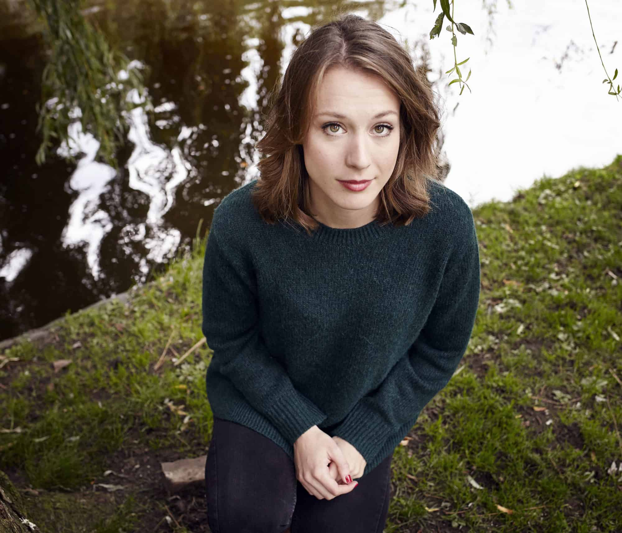 """Portrait of young woman crouching by pond in Amsterdam, close to Plantage. Wearing green pull over and looking straight into the camera."""
