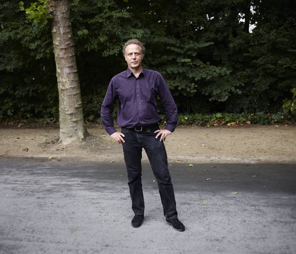"""""""Portrait of a middle aged Dutch man wearing black jeans and purple long-sleeved shirt. Standing on a path in a park in Amsterdam. Looking straight into the camera."""""""