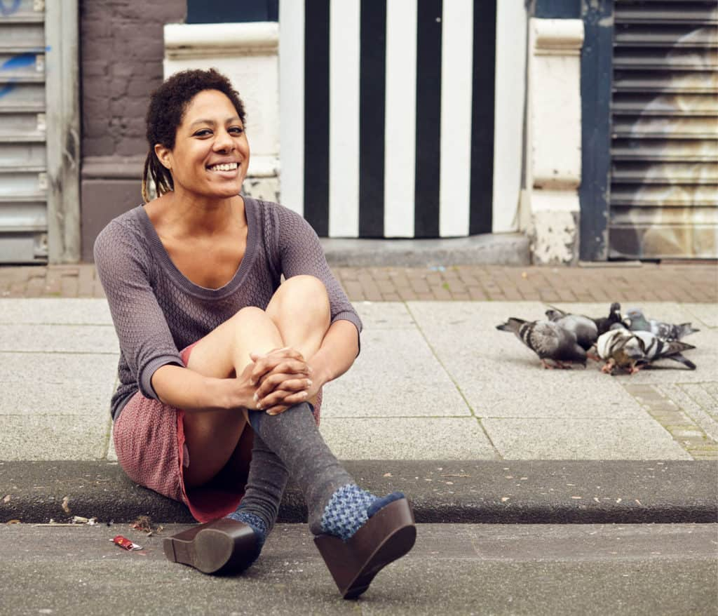 """""""Portrait of Dutch-Surinamese young woman, sitting smiling on the pavement in a market. Pigeons eating in the background."""""""