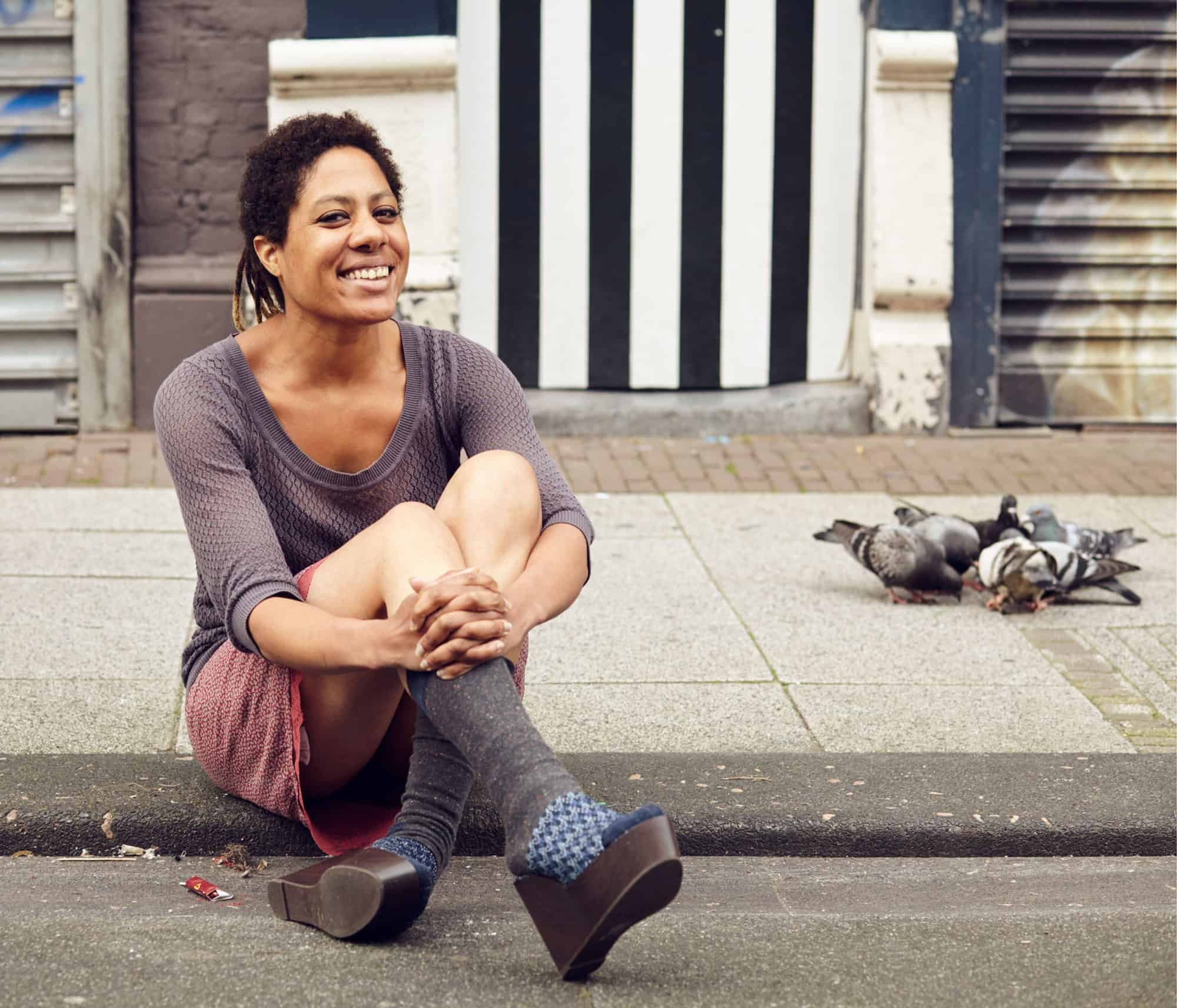 """Portrait of Dutch-Surinamese young woman, sitting smiling on the pavement in a market. Pigeons eating in the background."""