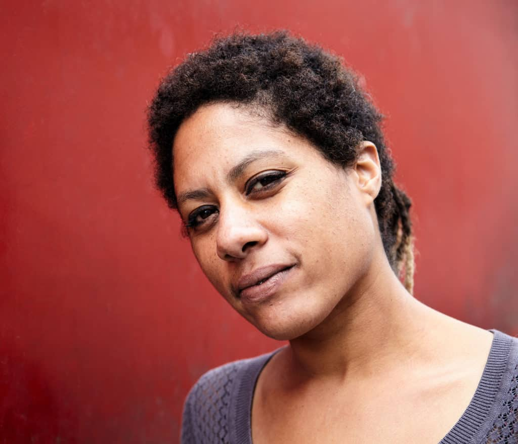 """""""Intimate portrait of a Raffaela Herbert, a Dutch-Suriname vocalist. Standing in-front of a weathered red wall."""""""