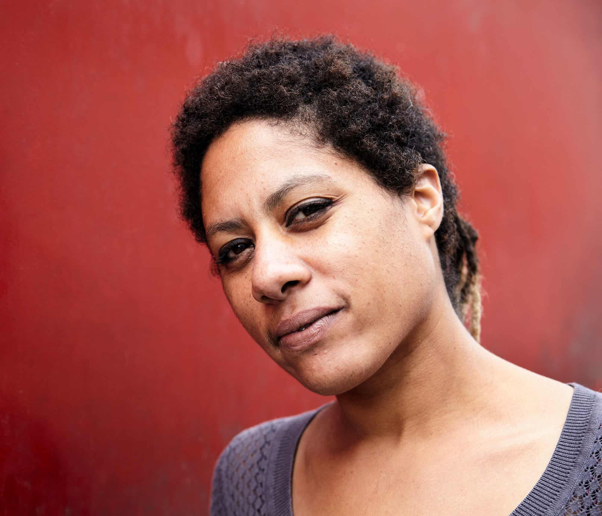 """Intimate portrait of a Raffaela Herbert, a Dutch-Suriname vocalist. Standing in-front of a weathered red wall."""