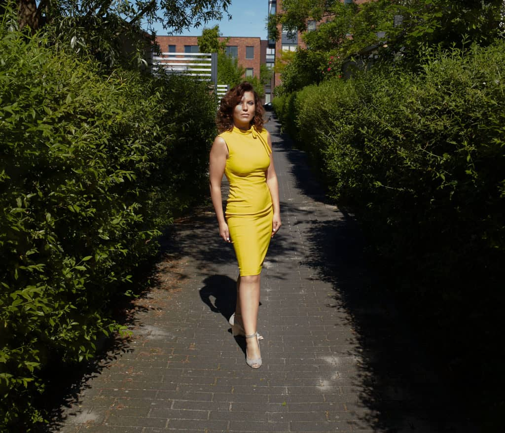 """""""Full length portrait of woman wearing yellow dress. Standing on a brick paved passage surrounded by green bushes."""""""