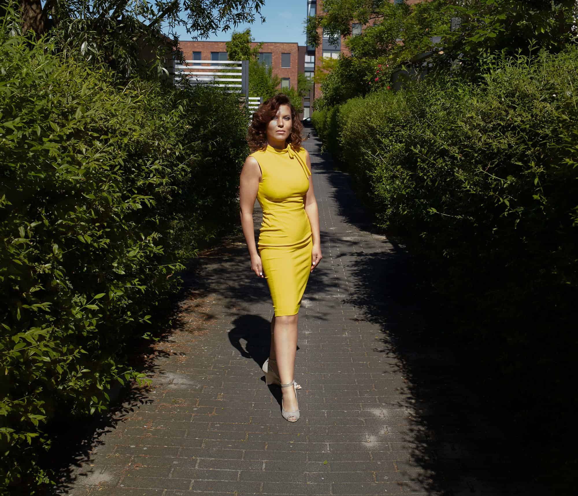 """Full length portrait of woman wearing yellow dress. Standing on a brick paved passage surrounded by green bushes."""