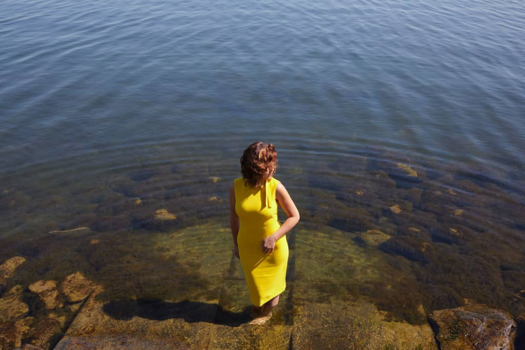 """""""Woman paddling barefoot in the water. Basking in the midday sun and wearing a yellow dress."""""""