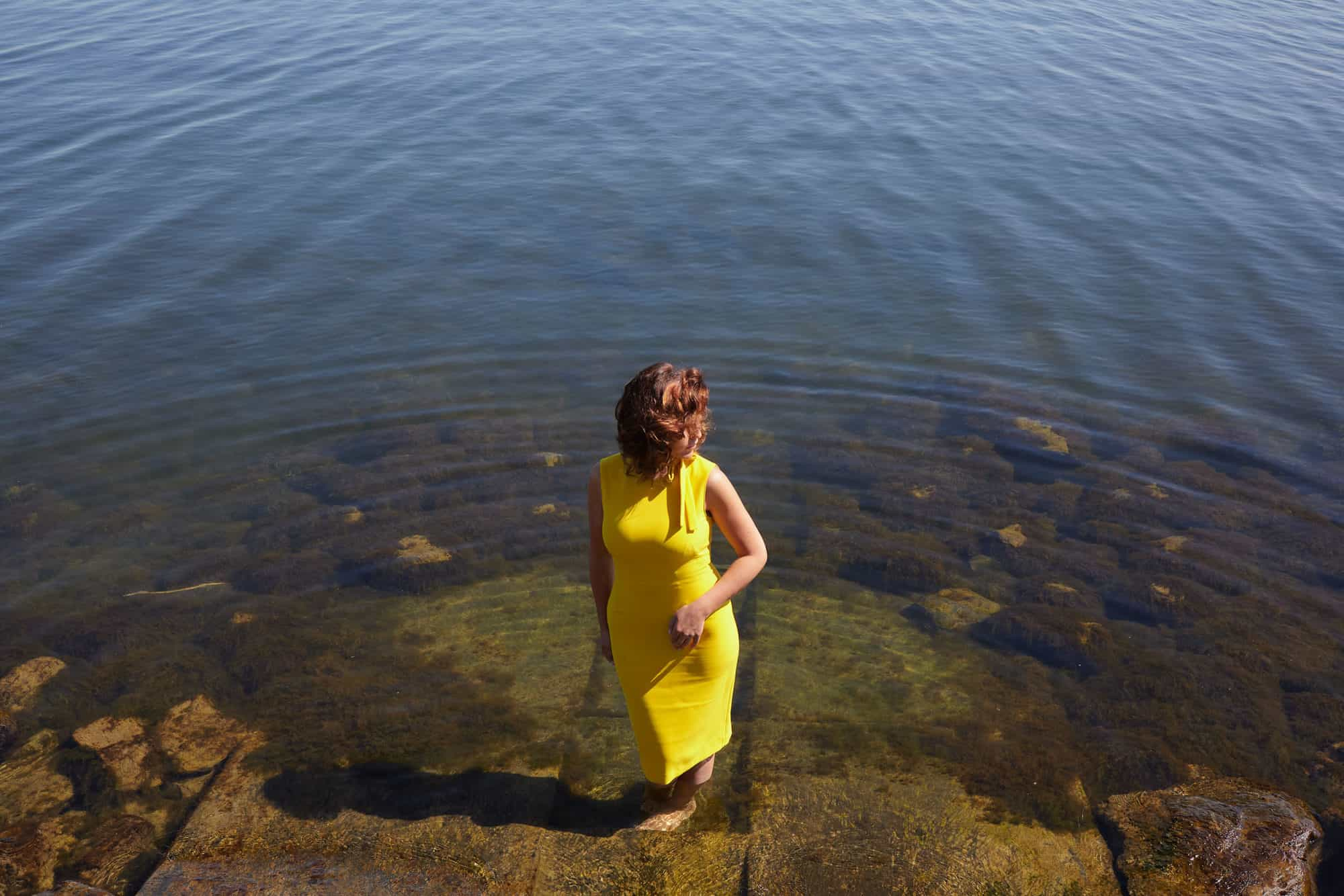 """Woman paddling barefoot in the water. Basking in the midday sun and wearing a yellow dress."""
