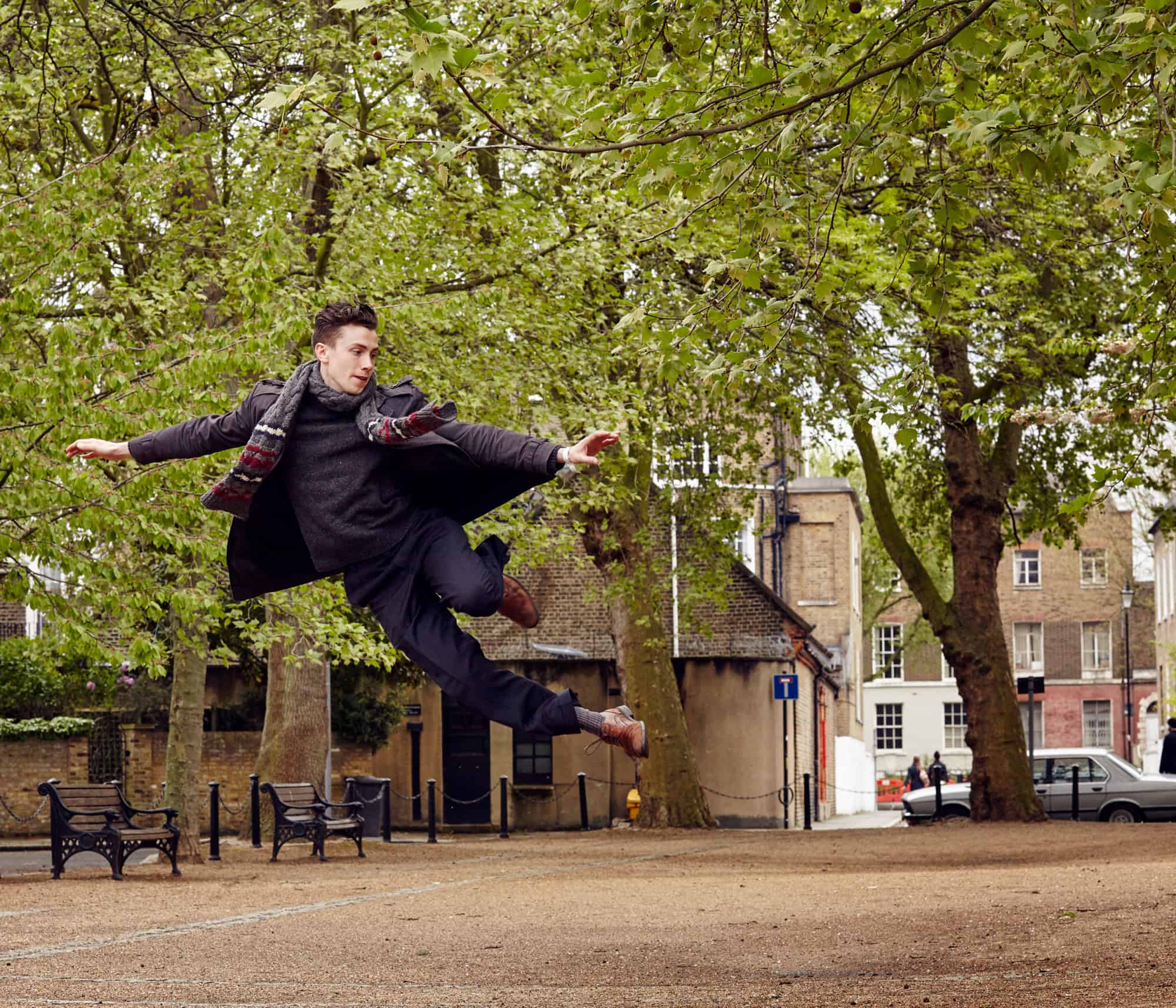 """Movement portrait. Man jumps high and gracefully in leafy square. Wearing winter coat and brown brogues. Car in background."""