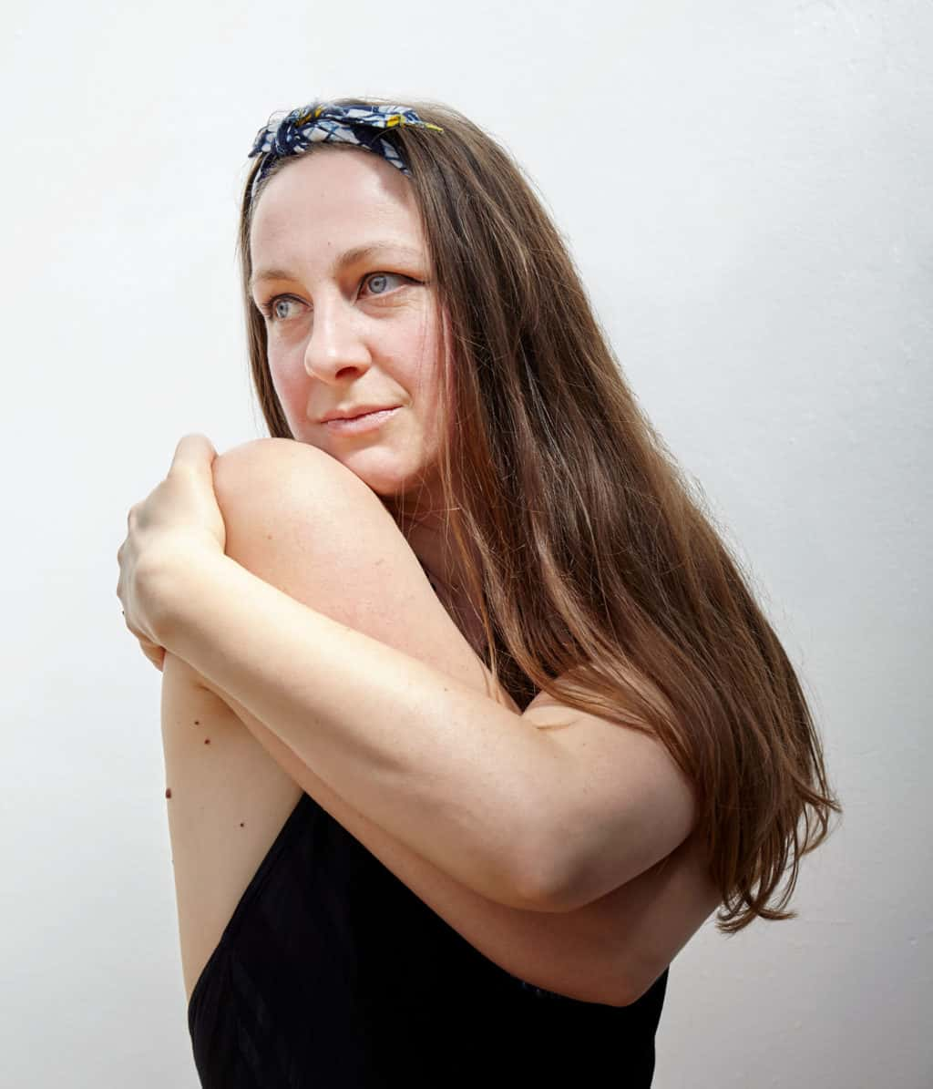 """""""Portrait of woman with long brown hair holding herself. Sculptural pose. Natural Daylight. Gazing off camera"""""""