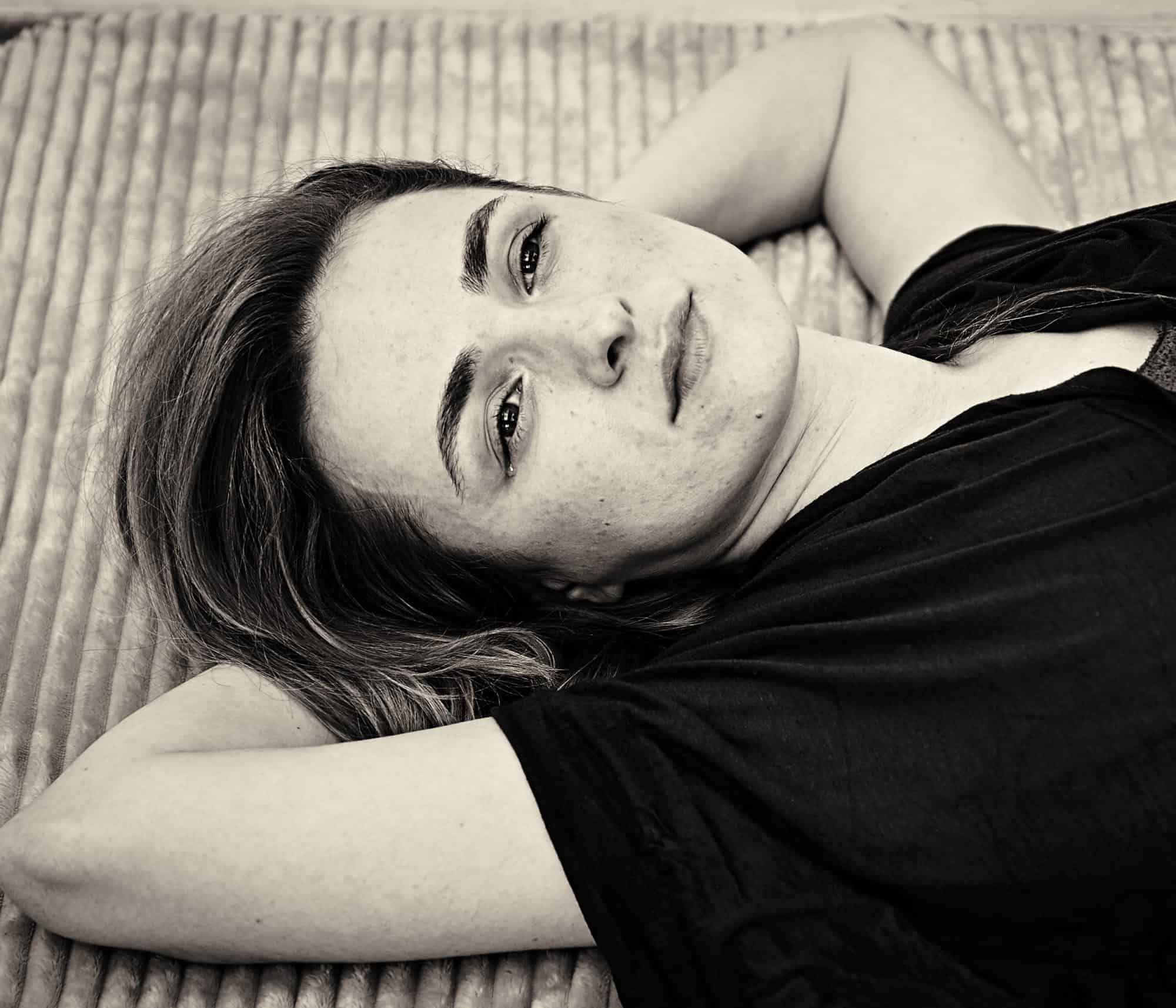"""Black and white intimate portrait of performer lying down. Tear in her eye, looking thoughtful."""