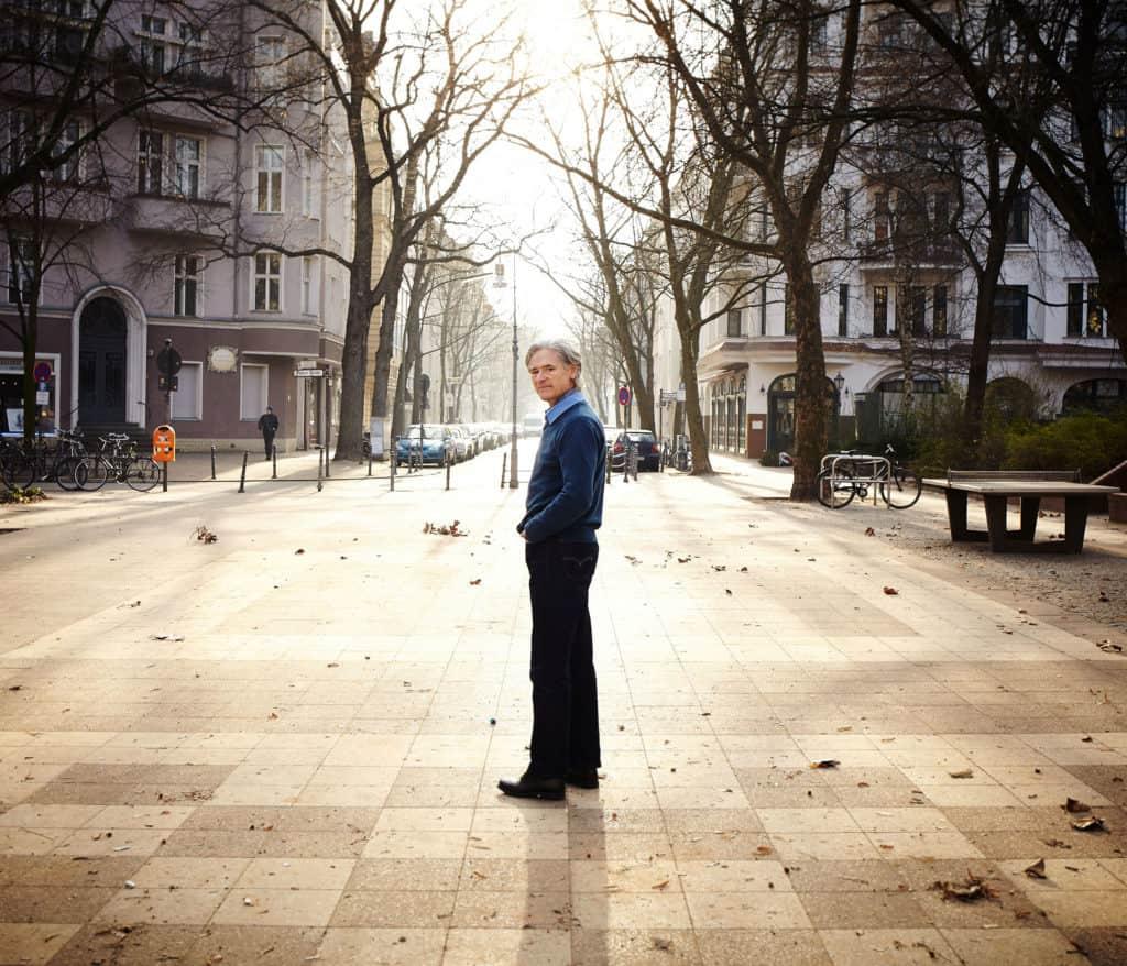"""Full length portrait of Uwe Paris standing in a square in West Berlin. Crisp winter daylight."""