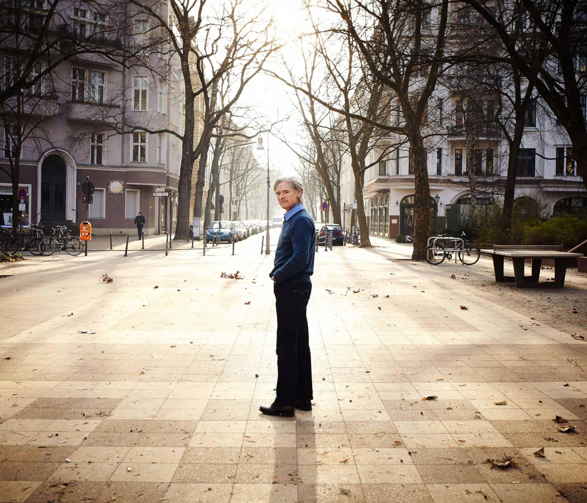 """Full length portrait of Uwe Paris standing in a square in West Berlin. Crisp winter daylight."""